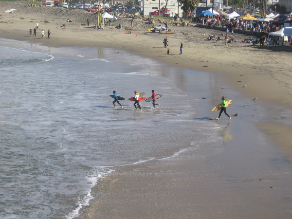 A horn sounds. The 10:30 heat is starting out across the beach! May the best surfer win!