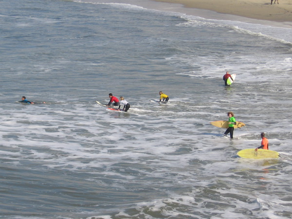 The surf competitors enter the water.
