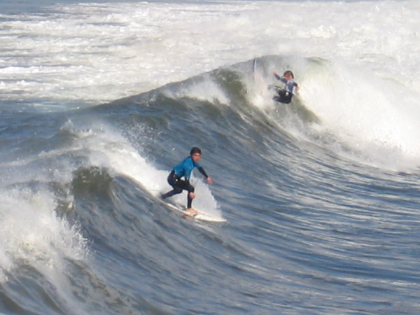 Two surfers tackle a good breaker!