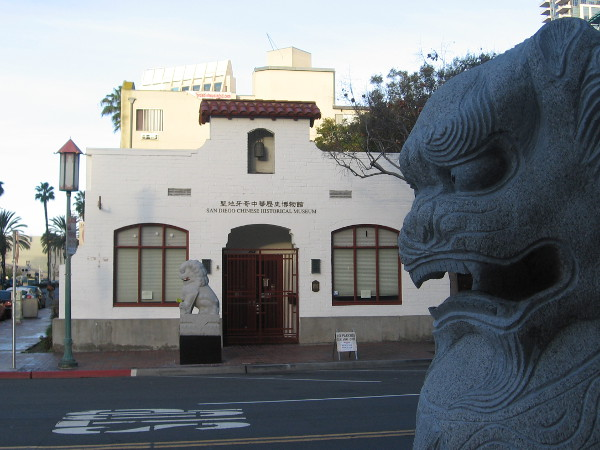 Gazing past stone lions at the entrance of the San Diego Chinese Historical Museum.