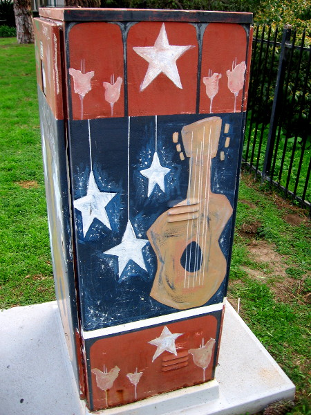 A guitar and stars decorate a utility box.