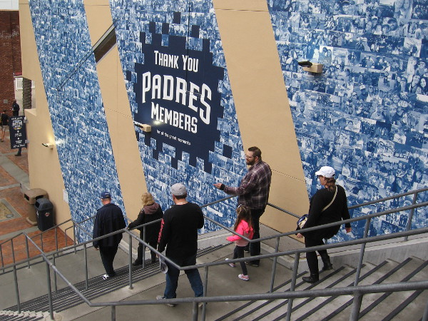 A family descends stairs near a thank you to Padres members.