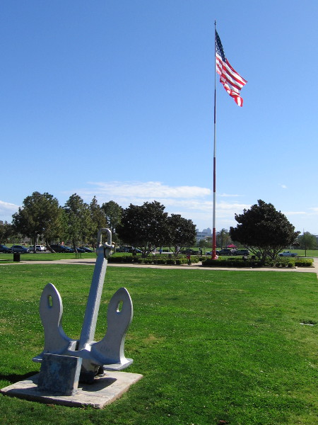An old anchor on display at Liberty Station. It sits across historic Preble Field from the American flag at full-mast.
