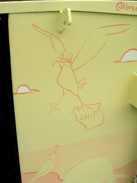 A funny sketch on an electrical box. A gull is carrying away a bag of chips!