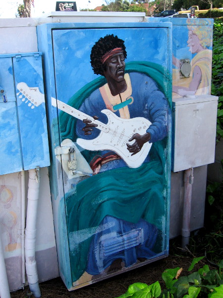 Jimi Hendrix plays electric guitar in heaven in colorful street art.