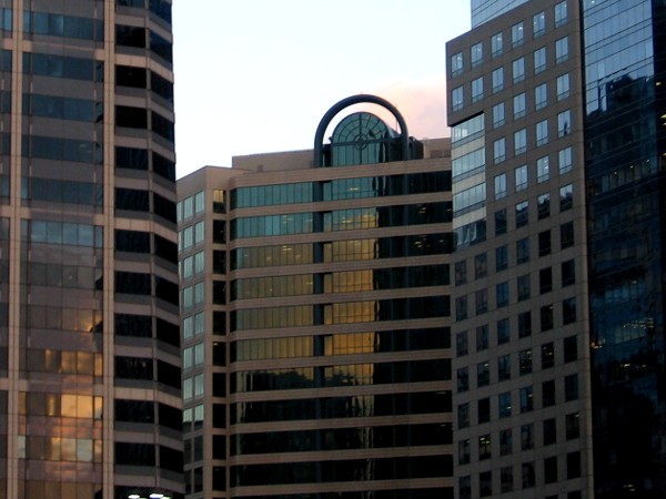 Sunset flames becomes glowing embers in the dark windows of several downtown skyscrapers.