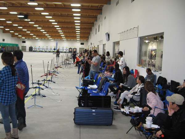 Participants and spectators against the back wall of the indoor archery range.