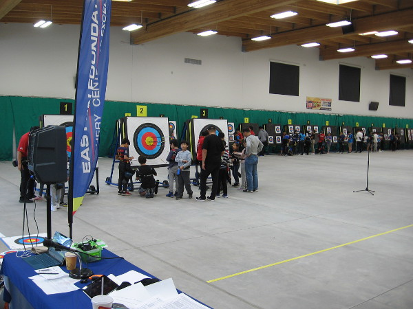 Youth learning archery skills check arrow positions on targets after a period of shooting.