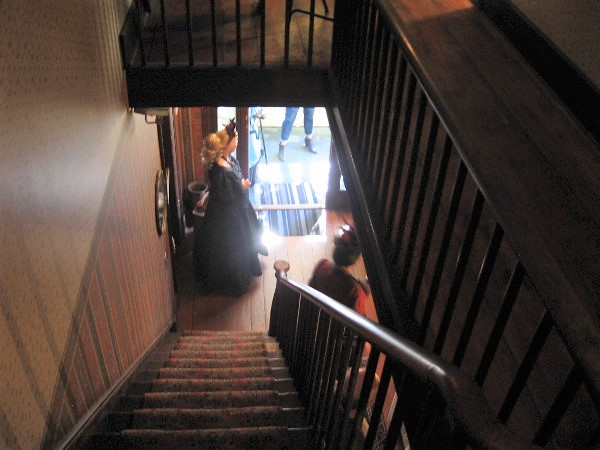 Looking down the stairs from the second floor. A lady in Victorian attire welcomes visitors to the museum during the Fall Back Festival in November.