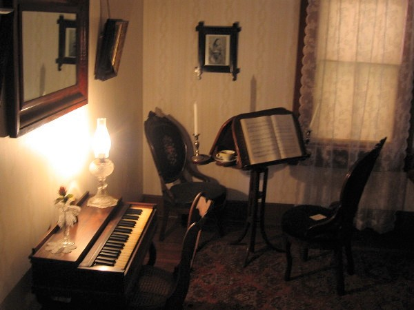 A small piano, sheet music, teacup and candle. Entertainment in the olden days was simple.