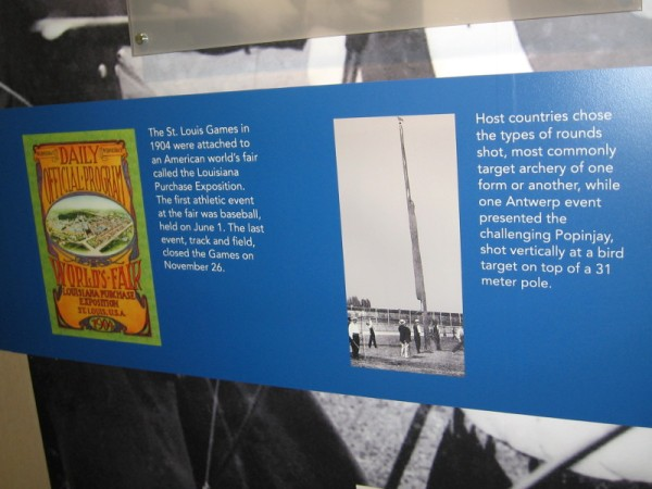 Early year displays include a 1904 program for the Louisiana Purchase Exposition and an early version of archery competition where the bird target sat atop a 31 meter pole.