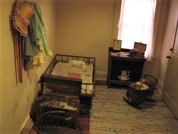 The nursery, with crib and small bed.