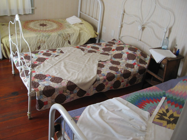 Three beds for the children have colorful quilts.