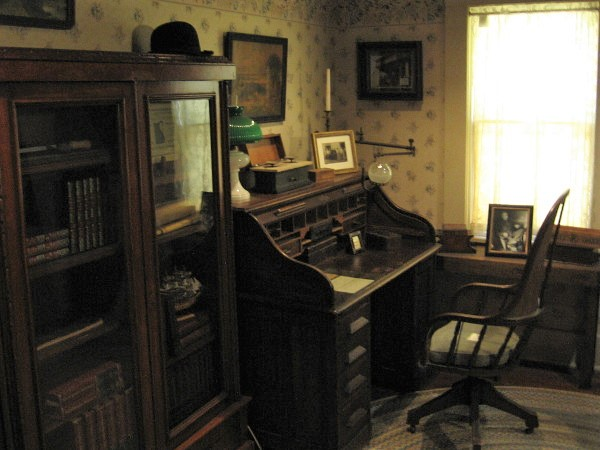 A desk in the study and a cabinet full of books.