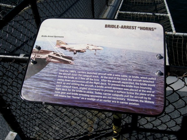 Sign at bow of USS Midway aircraft carrier explains the function of bridle-arrest horns. They were used until the 1980's. They are a vestige of an earlier era in carrier aviation.