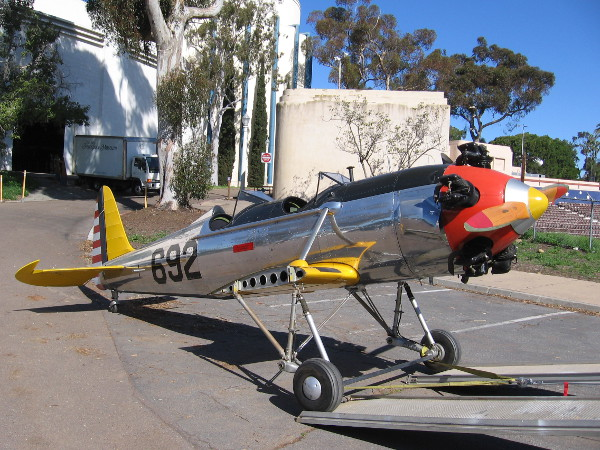 A shiny PT-22 military trainer aircraft from the World War II era is about to be towed from the San Diego Air and Space Museum to their annex at Gillespie Field.