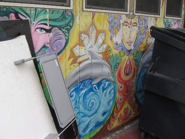 Cool street art faces in a Mission Beach alley peer from behind trash bins.