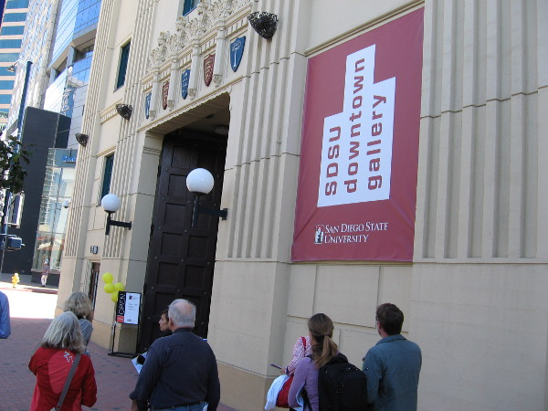 People walk along Broadway near the entrance of the SDSU Downtown Gallery.