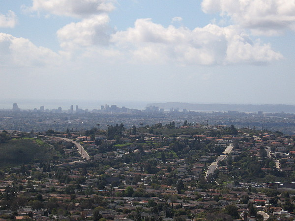 A zoomed photo. Downtown skyscrapers rise beside San Diego Bay. The Point Loma peninsula can be seen, as well.