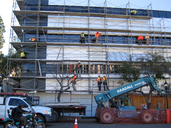 Workers on scaffolding renovate the exterior of a building on Sixth Avenue
