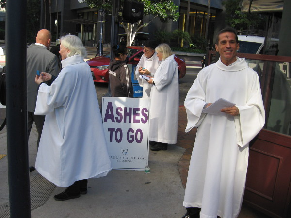Priests from St. Paul's Cathedral provide Ashes To Go and a blessing to anybody passing by on B Street on this Ash Wednesday.
