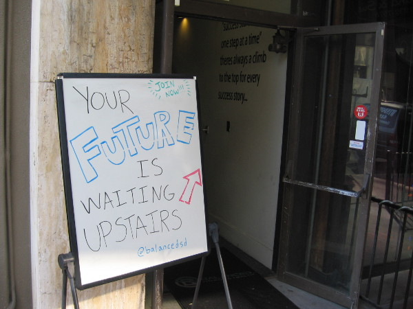 Sidewalk sign proclaims that your future is waiting upstairs!