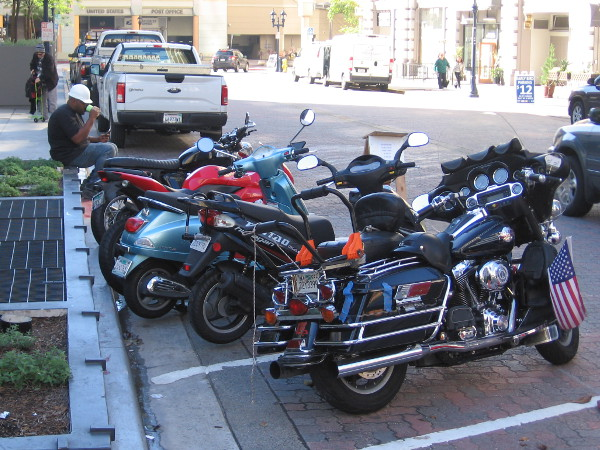 A row of motorcycles and a construction worker taking a break near Horton Plaza.