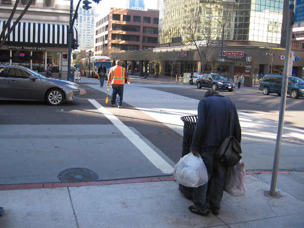 A worker crosses Broadway while a homeless man looks into a trashcan.
