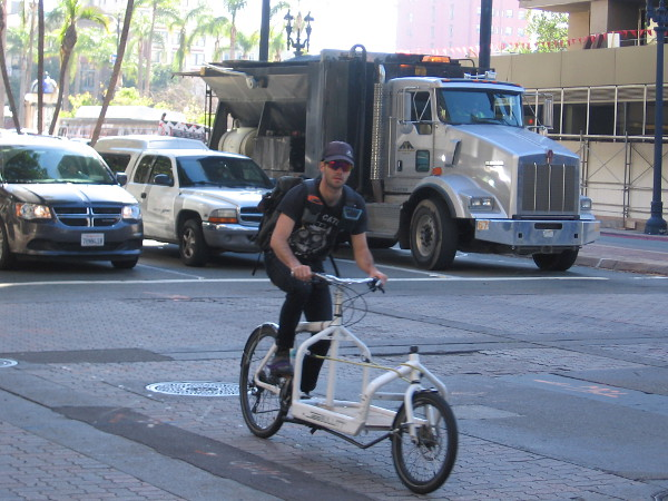 Here comes a guy riding a cool bicycle that appears to be designed for deliveries.