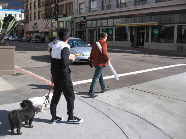 One guy crosses the street while carrying plans, another escorts dogs with a coffee in hand.