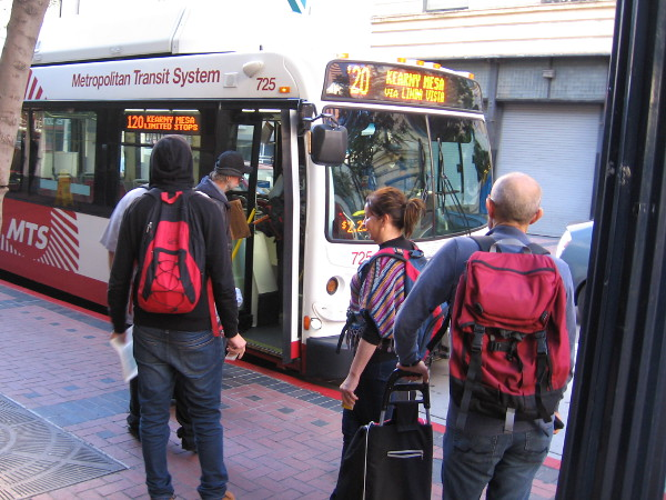 People board an MTS bus near the Fifth Avenue trolley station.