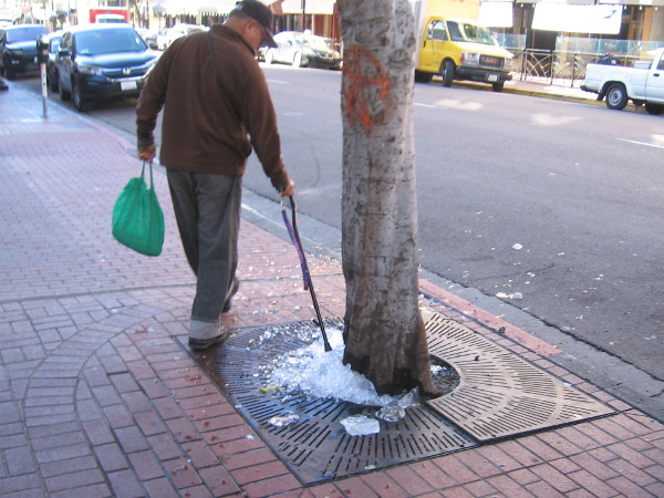 A walker runs his cane through some spilled leftover ice on a Gaslamp sidewalk.