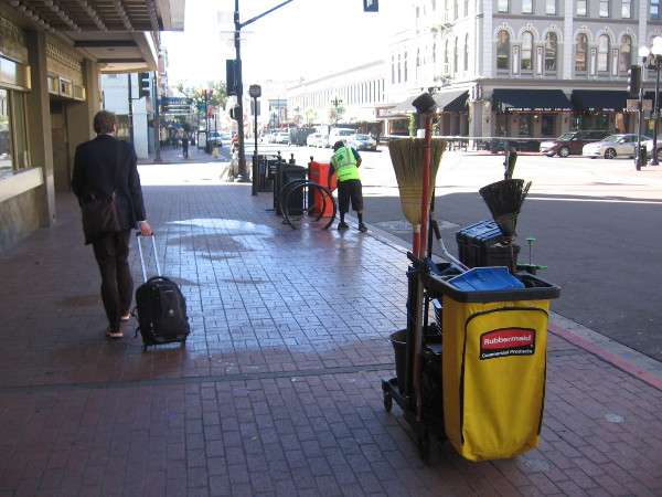 A worker with Clean and Safe's downtown program mops the sidewalk while a businessman walks by.