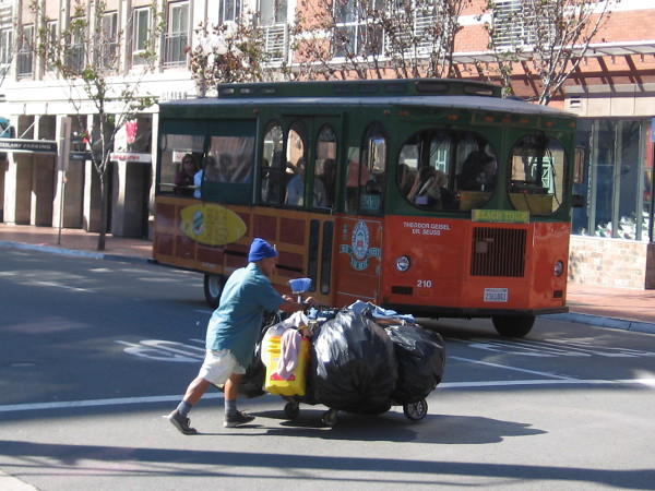 An Old Town Trolley Tours vehicle loaded with tourists waits for a homeless man with a packed shopping cart to clear a downtown intersection.