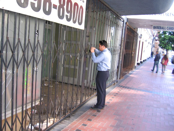 Someone unlocks the security gate in front of a small downtown shop. It is morning, so time to open.