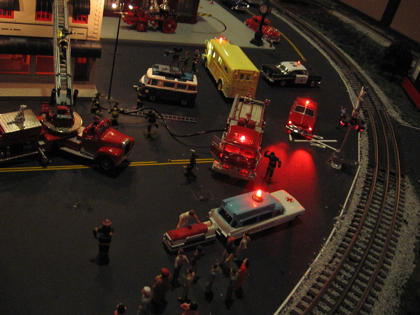 A detailed scene recreates firemen fighting a fire at night.