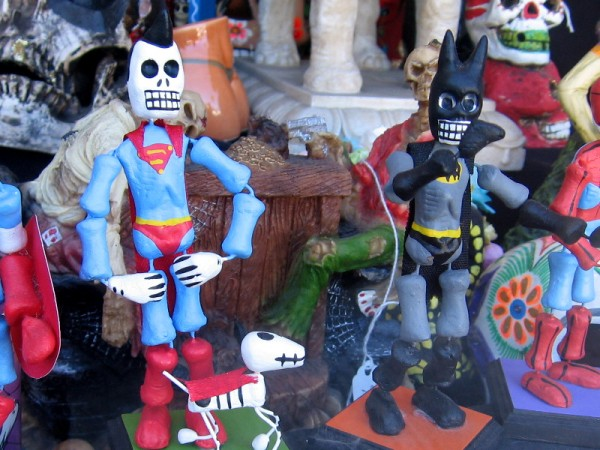 Fun skeleton artwork celebrating Day of the Dead (Día de los Muertos). The figures are Superman, his dog Krypto, and Batman!
