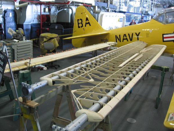 A tour of the USS Midway Museum often includes aircraft that are undergoing maintenance or restoration. Three helicopter rotors are being reconstructed here.