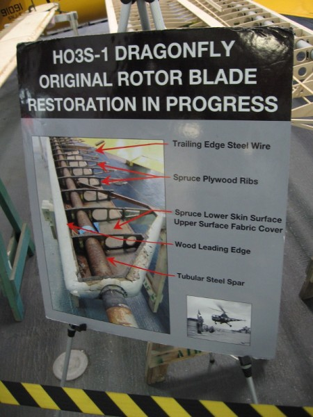 Sign on hangar deck of USS Midway describes the HO3S-1 Dragonfly's original rotor blade restoration, which is in progress.