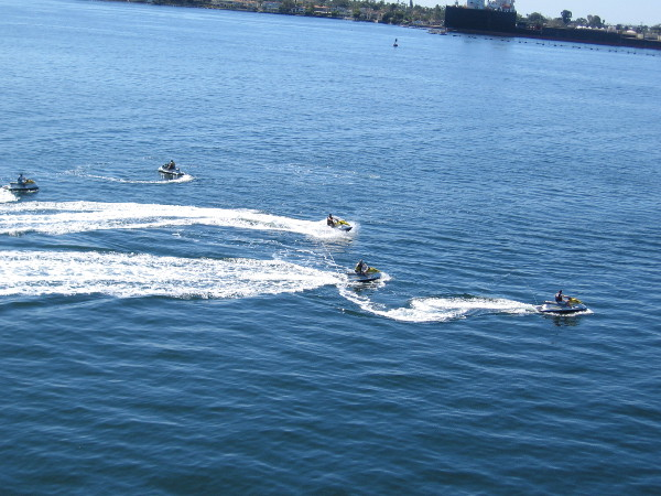 Five people were jetting around the bay on some fun personal watercraft.