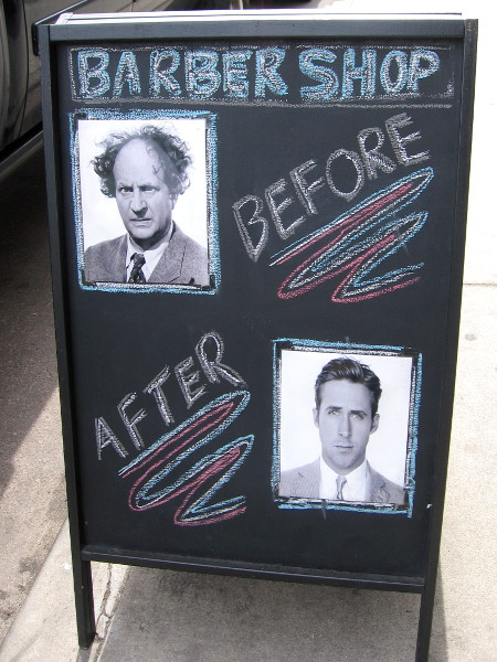 A humorous sign on the sidewalk. Head into this barber shop and come out a completely different person!