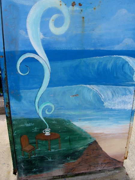 Street art on a utility box. The curl of this coffee's steam resembles the surf beyond the sand.