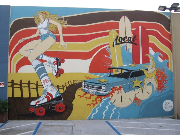 A cool mural near The Local Pacific Beach, painted in 2016 by artists Sean Dietrich and Kai Martin. A blonde on roller skates, the PB boardwalk, beach, and a very strange car.