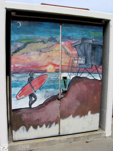 Street art on storage doors shows a surfer climbing toward a lifeguard tower at sunset.