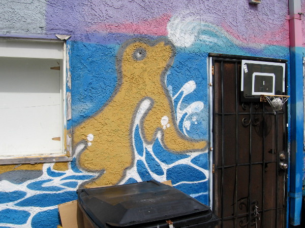 A spray painted sea lion near a door in the alley.