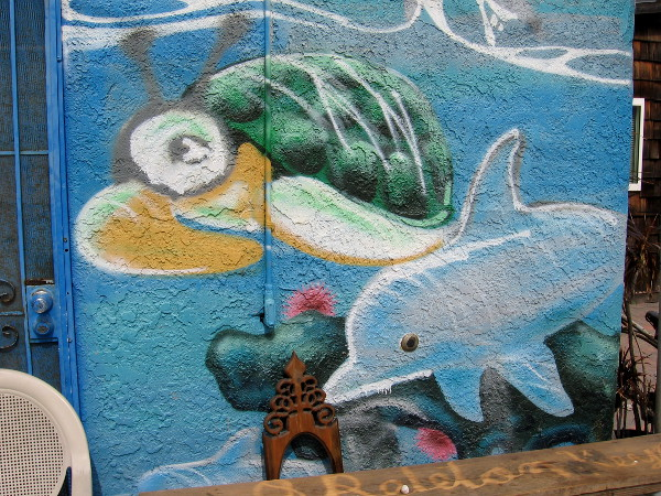 A sea turtle and dolphin swim across a wall.