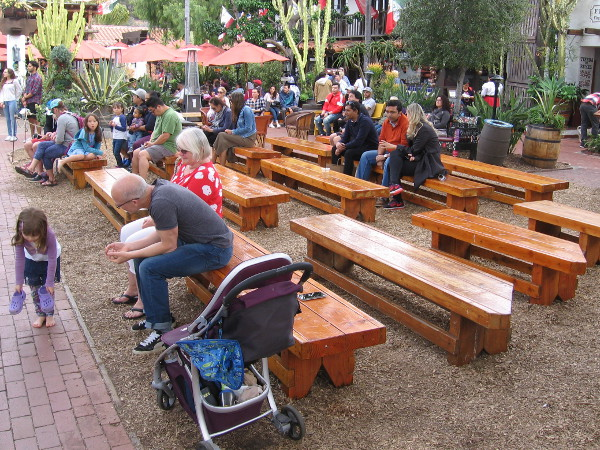 Outdoor benches at Fiesta de Reyes allow visitors to relax and watch the free entertainment.