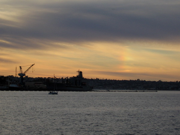 A slight rainbow appears at sunset above Point Loma.