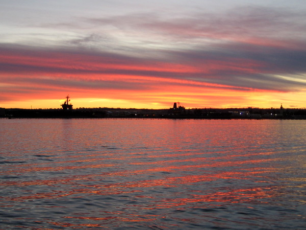 The sunset turns fiery, painting the rippled water of San Diego Bay red.