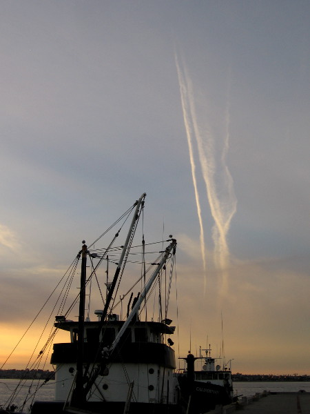 Aircraft condensation trails catch the sun high in the sky, as light fades around fishing vessels docked at the G Street Pier.
